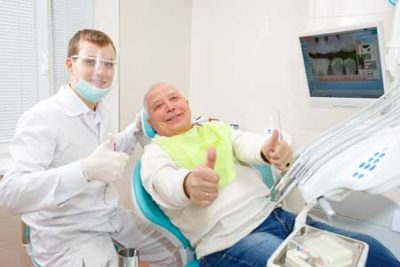 man with dentist preparing for oral surgery