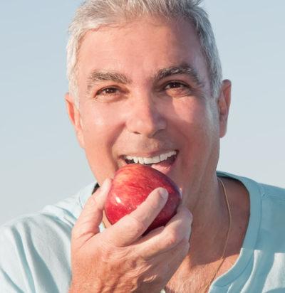 older man eating an apple after getting dentures