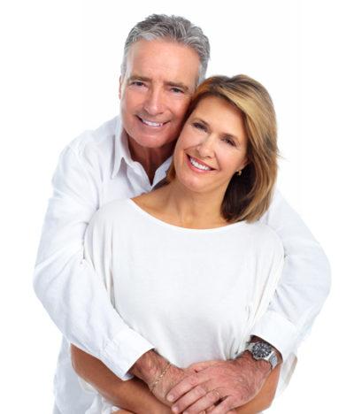 senior couple smiling after getting dental bridges
