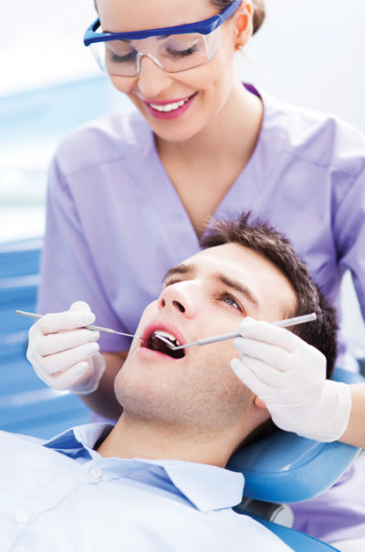 man with dentist getting endodontics therapy