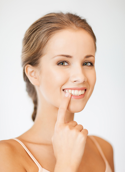 girl smiling pointing to her teeth