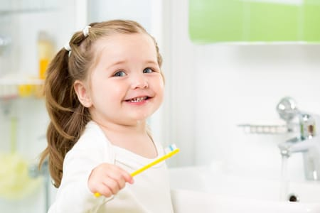 young child smiling after no cavities visit from the dentist
